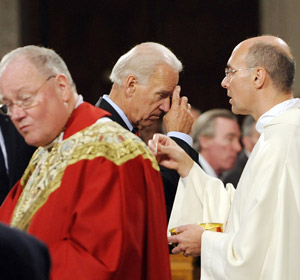 V. P. Biden blesses himself after receiving communion at St. Patrick's.  Cardinal Dolan looks the other way.