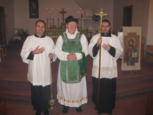 Father Cornelius with acolytes John (left) and Chris at the farewell Mass at the Ordinariate.